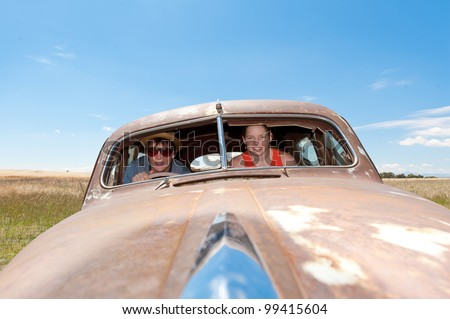 Young guy and girl in a rusty old car - stock photo