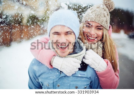 Young guy and girl in winterwear enjoying snowfall - stock photo