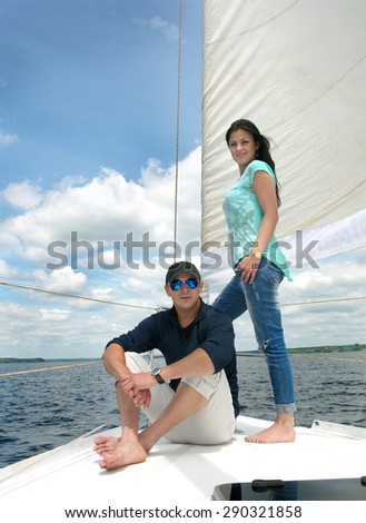 young guy and girl on deck of the yacht under sail  - stock photo