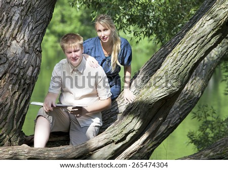 Young guy and the girl with textbooks on the bank of lake - stock photo