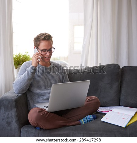 Young guy at home on his couch talking on the phone and smiling while looking at his laptop resting on his lap - stock photo