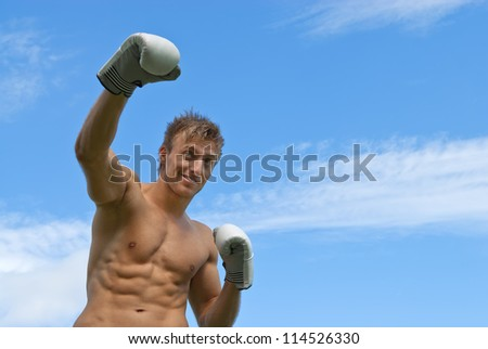 Young guy boxing. Outdoor training under blue sky.