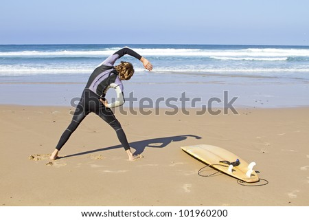 Young guy doing exercises before going to surf - stock photo