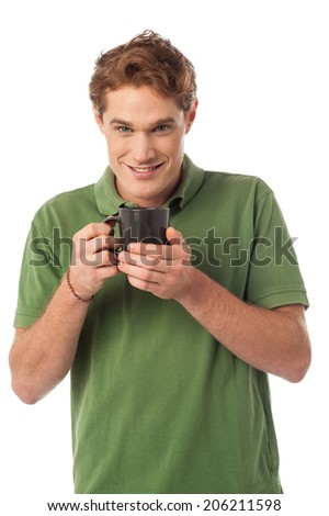 Young guy gets warm with a cup of coffee - stock photo