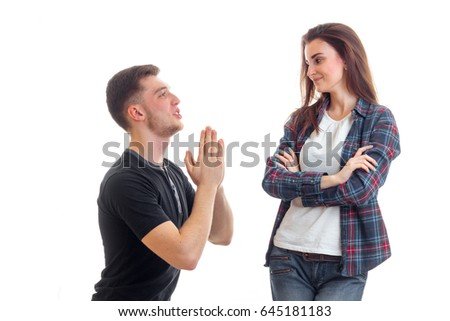 young guy hands and asks forgiveness of a beautiful girl who looks at him and smiling