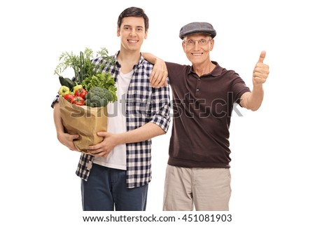 Young guy helping a senior man with groceries isolated on white background
