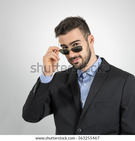 Young guy holding and looking over sunglasses. Desaturated portrait over gray studio background with retro vignette.