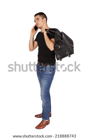 Young guy holding bag talking on his mobile on a white background