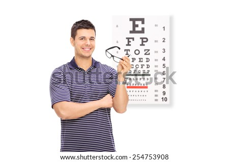 Young guy holding glasses in front of an eye chart isolated on white background