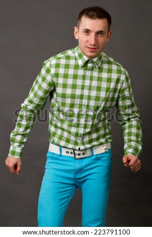 young guy in a checkered shirt on a gray background - stock photo