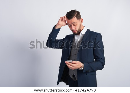 young guy in a suit upset by the information in the phone - stock photo