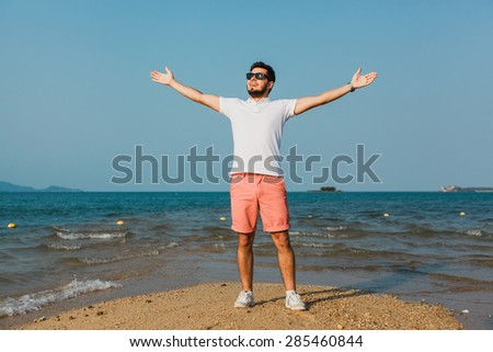 young guy in a white t-shirt and sunglasses raised his hands high up celebrates victory and winning