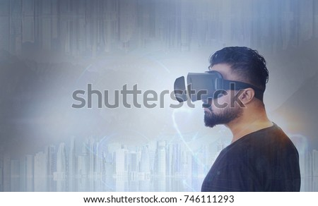 Young Guy in black t shirt looking through VR (Virtual Reality) glasses -