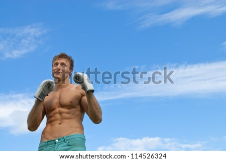 Young guy in boxing gloves training outdoors under the blue sky.