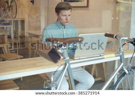 Young guy in cafe working for laptop and coffee