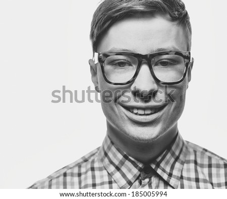 Young guy in eyeglasses smiling and looking at camera