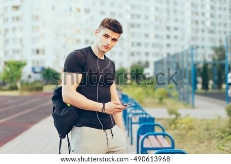 Young guy in sport black T-shirt and gray sport pants is standing on city and stadium background. He is listening to music through headphones, holds sport bag and looking to camera.