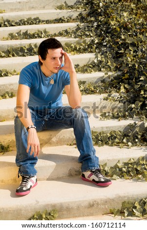 Young guy in thoughtful attitude sitting on  some stairs - stock photo