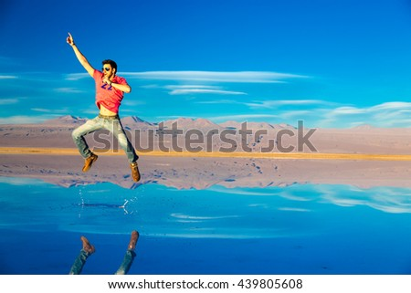 Young guy jumping on a exotic place in Atacama Desert, Chile - stock photo