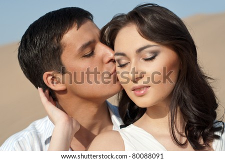 Young guy kissing a beautiful young girl. Young couple in white