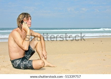 Young guy making a phone call sitting on the beach - stock photo