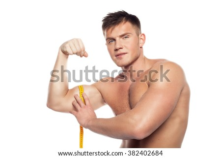 young guy measures the inflated biceps