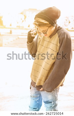 young guy outdoor with rasta hair with smart phone in a lifestyle concept with a warm filter applied selective focus on glasses - stock photo