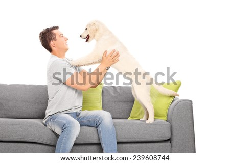 Young guy playing with his dog isolated on white background   - stock photo