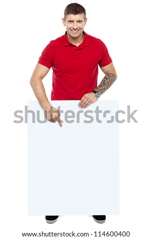 Young guy pointing at the billboard, full length shot over white background