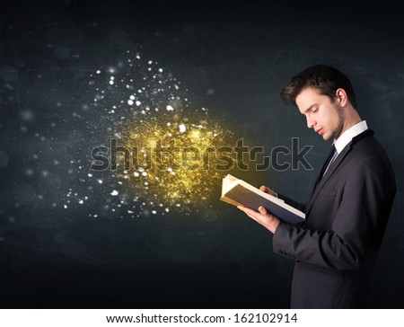 Young guy reading a magical book in front of a blackboard