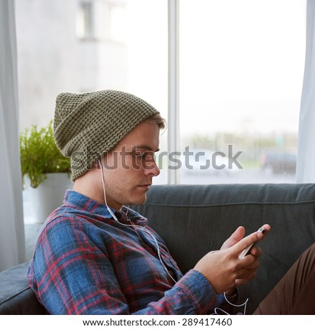Young guy relaxing on his couch at home with earphones in playing music on his phone - stock photo