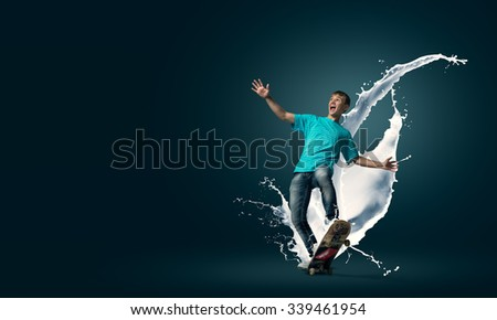Young guy riding skateboard and paint splashes from under wheels - stock photo