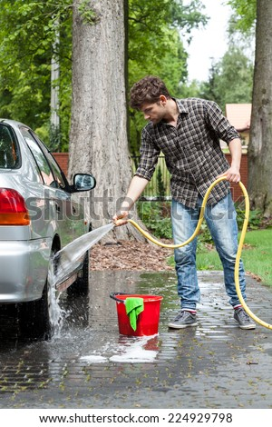Young guy rinsing the soap of the car wheel by stream of water - stock photo