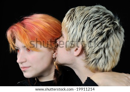 Young guy says soft words to his girlfriend, on black background