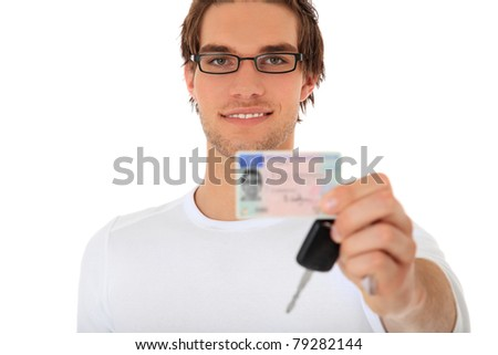 Young guy showing his drivers license and car keys. Selective focus on person in background. License details are blurred out. All on white background. - stock photo