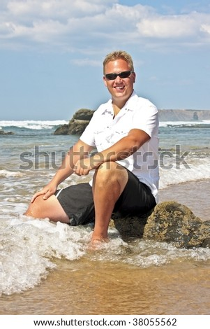 Young guy sitting on a rock at the atlantic ocean