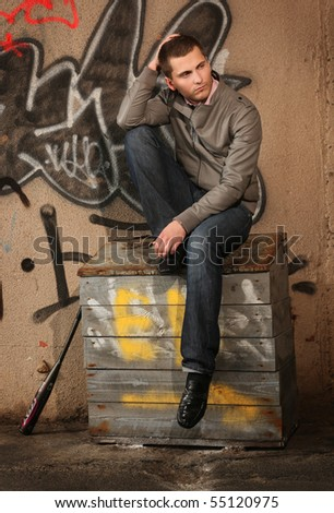 young guy sitting on the sand box ner painted wall - stock photo