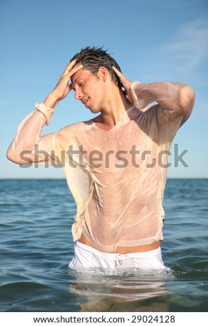 Young guy standing in sea sky