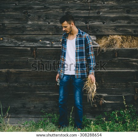Young guy standing outside of old barn. Vintage retro style effect, soft and selective focus, low light, grain texture visible on maximum size. - stock photo