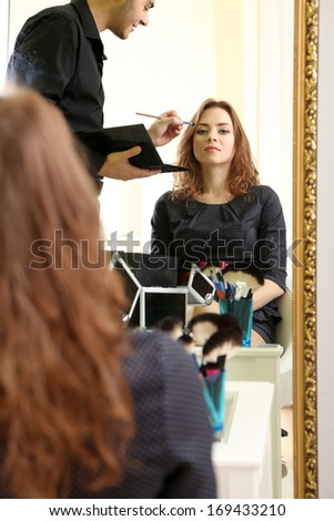 Young guy stylist doing makeup beautiful woman in beauty salon  - stock photo