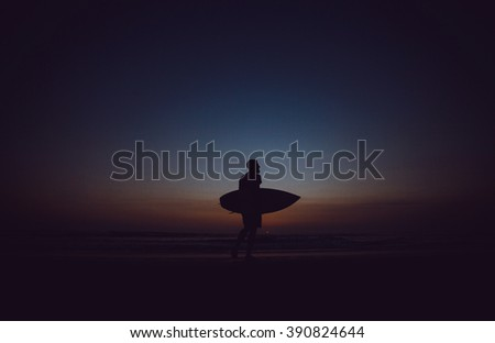 young guy true surfer, professional, with nice body posing with a surf Board on the ocean, victoriously raises his hand up, a beautiful sunset, surfing, big waves,outdoor portrait, close up - stock photo