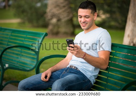 Young guy using his cellphone at the park - stock photo
