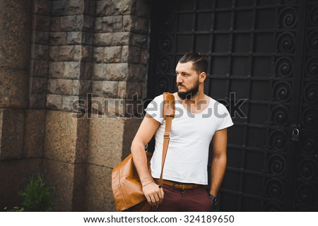 young guy with a beard and mustache  and white T-shirt  posing on the street  vintage man, fashion men, hipster street casual  leather bag and hours against the background of a brick wall - stock photo