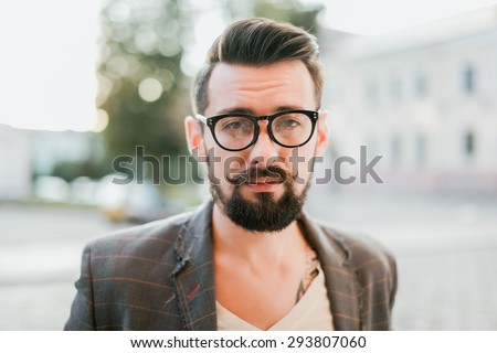 young guy with a beard and mustache with glasses in a suit posing on the street in the sunlight, fashion man, style, vintage style, retro men, handsome beard, outdoor portrait, close up - stock photo