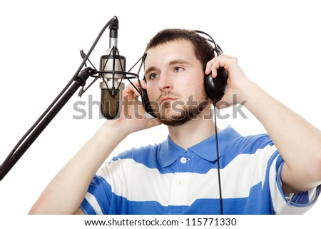young guy with a beard, writes a song with headphones and a microphone, isolated on white background.