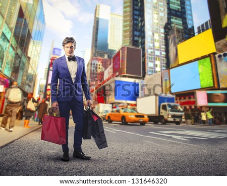 young guy with a lot of bags goes shopping in New York - stock photo