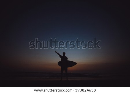 young guy with a sports figure posing with a surf Board on the ocean, victoriously raises his hand up, a beautiful sunset, surfing, big waves,outdoor portrait, close up - stock photo