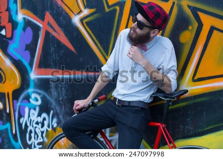 Young guy with beard standing next to a graffiti wall with a bicycle. - stock photo