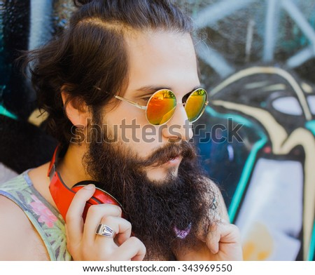 young guy with long hair mustache and beard listening to music with headphones,young guy with a beard and mustache with glasses in the sunlight, fashion man, style, vintage style, retro men - stock photo