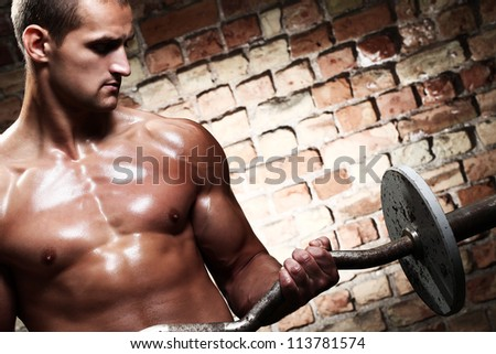 Young guy with muscular body with barbell over brick wall - stock photo